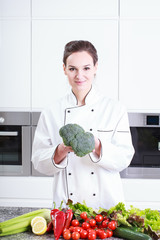 Young chef showing broccoli