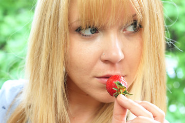 close-up beautiful blond woman eats a strawberry