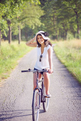Smiling young woman biking on a country road