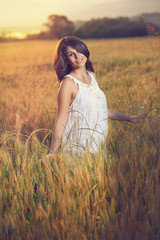 Beautiful woman poses in a field