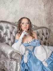 Beautiful woman in medieval dress on the sofa