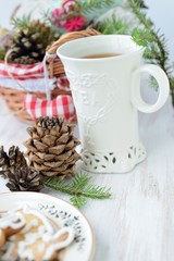 Christmas composition with a cup of tea, fir cones and cookies.