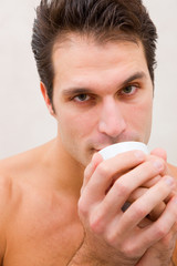Man in spa holding cup near mouth