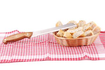 Bread slices in basket on tablecloth.