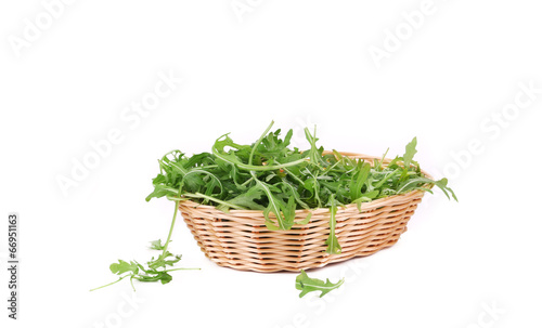 Bunch of arugula in basket.