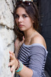 Girl in striped shirt by stone wall