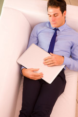 Businessman sleeping couch holding laptop