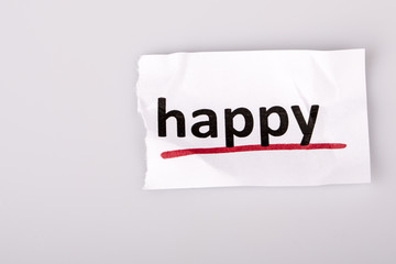 The word happy on torn paper