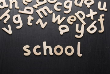 Wooden letters spell school on a blackboard