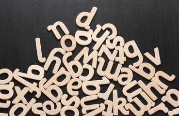 Random wooden letters piled up on a blackboard surface