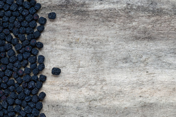 Dried aronia berries on wooden background