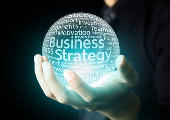 Businessman hand showing business strategy word in crystal ball