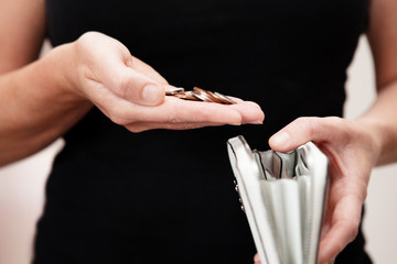 woman holding coins over purse