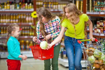 Две девушки и ребенок в продуктовом магазине