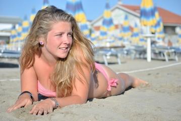 Giovane ragazza sdraiata sulla sabbia al mare