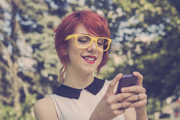 Hipster girl text messaging on her smart phone, retro colors