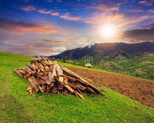 lumber on agriculture field in mountains at sunset