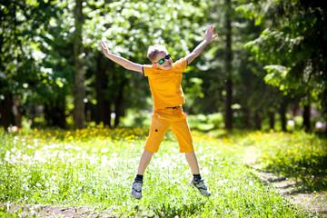 Мальчик в прыжке на полянке