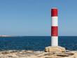 Red and white colored column at the coastline of Malta