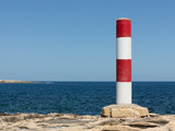 Red and white colored column at the coastline of Malta