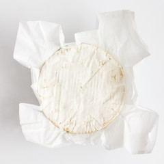 White round cheese with mould shot from above. On white surface.