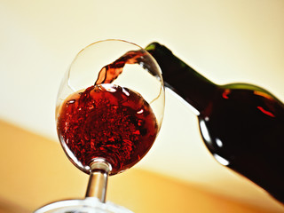 Rotwein wird in ein Glas eingeschenkt