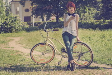 Hipster teenage girl on her vintage bike, listening to the music