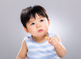 Asian baby boy eat cookie