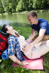 Boy tickling girl by the lake
