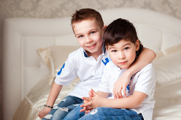 two boys sitting on the bed