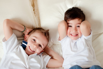 Two boys having fun in bed at home