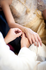 groom wearing gold bracelet for his bride in wedding ceremony