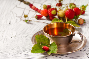 Wild strawberry tea in a gold cup