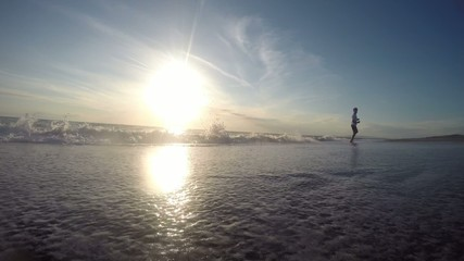 Man running on the beach at sunset. Sunny summer day