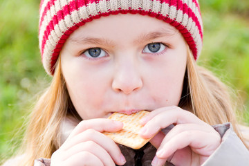 Girl in autumn eating cookie