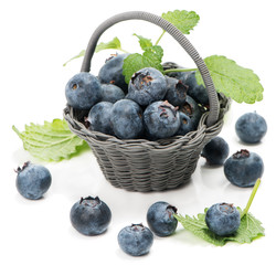 Blueberries with leaves of mint in a little basket