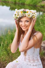 Cute young woman with circlet of camomile at the riverside