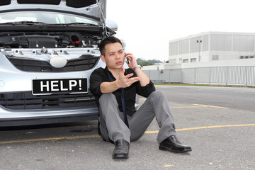 A man calling for help to repair a stalled car