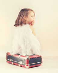Sad little girl with a suitcase