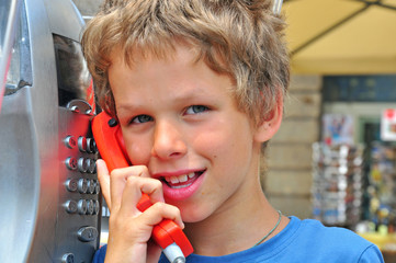 Smiling boy talking by public phone