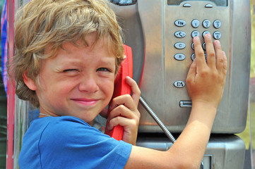 Small child talking by public phone