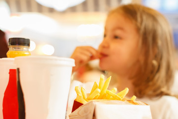 Little girl eating fast food french fries