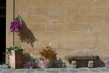 Flower pot ,seat and old brick wall in Pienza,Tuscany, Italy