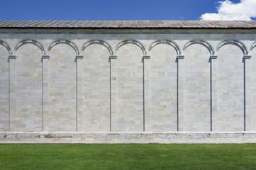 Luxurious wall with graceful columns and arches in Pisa, Italy