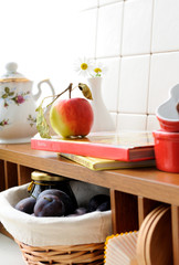 Open shelf at the kitchen with tableware and a fruit.