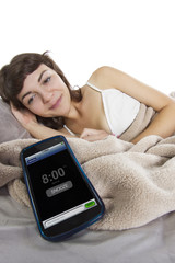 female snoozing modern cell phone alarm clock