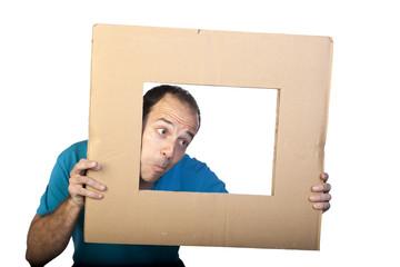 Hombre sacando la cabeza por marco de cartón
