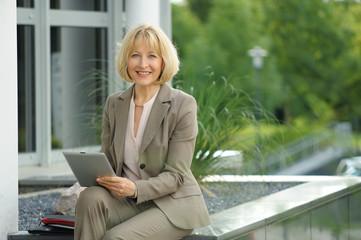 Reifere Geschäftsfrau mit Tablet PC