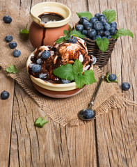 White ice cream with berries and leaf of mint and chocolate jam