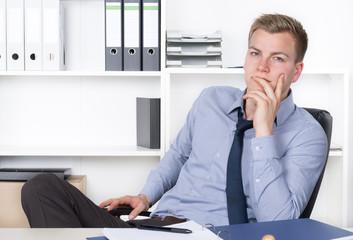 Junger nachdenklicher Mann sitzt am Schreibtisch im Büro